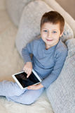 Little boy with iPad. Sitting on the sofa Royalty Free Stock Photography