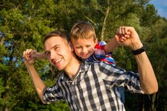 Free Little Boy Is Sitting On Shoulders His Dad While Imitating The F Royalty Free Stock Images - 122643699
