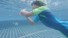 Little Boy ist blaue Schwimmenklagenschwimmen im Tauchen im Swimmingpool stock video footage