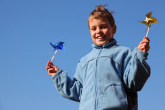Little boy in jacket with pinwheels in his hands stock photos