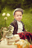 Little boy in a jacket and plaid pants to sit on the cushion, ne Royalty Free Stock Images