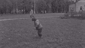 Little boy in jacket run and pick grass from ground in spring park. People walking. Trees. Smile. Little boy in jacket run and pick grass from ground in spring stock video footage