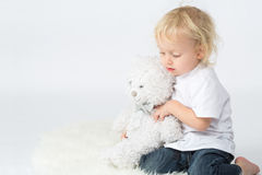 The little boy in jeans with a bear in his hands playing Royalty Free Stock Photo