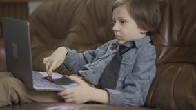 The little boy in jeans jacket sitting on the leather sofa playing on the laptop. The leisure of modern child. Addiction stock video footage