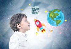 Little boy in jeans and shirt, space travel