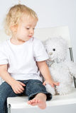 The little boy in jeans with a toy bear sits Royalty Free Stock Photography