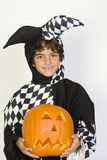 Little Boy In Jester Outfit Holding Jack-O-Lantern Stock Photography