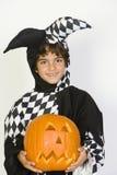 Little Boy In Jester Outfit Holding Jack-O-Lantern. Portrait of a cute Hispanic boy in jester outfit holding Jack-O-Lantern isolated over white background Stock Photography