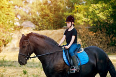 A little boy jockey on horseback . Horseback riding lessons . Stock Photo