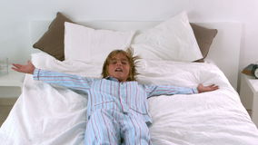 Little boy jumping back onto bed Royalty Free Stock Images