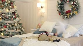 Little boy jumping on bed near the New Year tree. Little cheerful boy jumping on the bed and throwing a pillow on the background of the New Year tree stock video footage