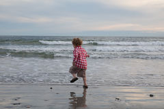 A little boy is jumping and dancing by the ocean stock photos