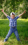Little boy jumping on the green grass in the park Royalty Free Stock Image