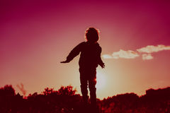 Little boy jumping from joy in sunset nature Royalty Free Stock Image