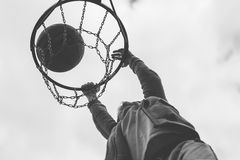 A little boy jumping and making goal playing streetball, basketball. Throws a basketball ball in the ring. The concept of sport Royalty Free Stock Photography