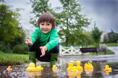 Little boy, jumping in muddy puddles in the park, rubber ducks i Royalty Free Stock Image