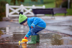 Little boy, jumping in muddy puddles Stock Photography