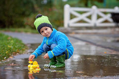 Little boy, jumping in muddy puddles Royalty Free Stock Image