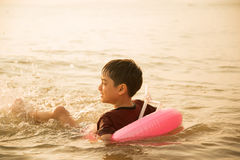 Little boy jumping over the beach wave Stock Images