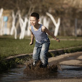 Little boy jumping in puddle Stock Photos