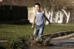 Little boy jumping in puddle Royalty Free Stock Images