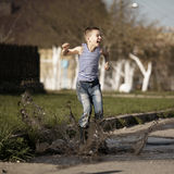 Little boy jumping in puddle Royalty Free Stock Image
