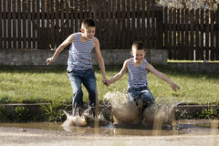 Little boy jumping in puddle Stock Image