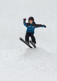 Little boy jumping on snow skis. Child snow skiing and jumping Royalty Free Stock Photos