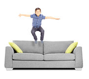 Little boy jumping on a sofa. Isolated on white background Royalty Free Stock Images