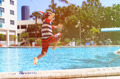 Little boy jumping into swimming pool Royalty Free Stock Photos