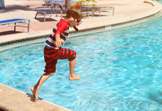 Little boy jumping into swimming pool. Happy little boy jumping into swimming pool, family vacation Stock Images