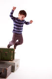 A little boy jumps from a boxes on a white background Stock Photos