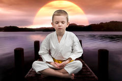 Little boy karate meditates,relaxes sitting on the bridge on the river. Exercise in the open air. The winner of the athlete. Athlete, karate,meditation on the stock photography