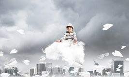 Little boy keeping mind conscious. Young little boy keeping eyes closed and looking concentrated while meditating on cloud among flying paper planes with Stock Image