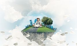 Little boy keeping mind conscious. Young little boy keeping eyes closed and looking concentrated while meditating on flying island among flying paper planes Royalty Free Stock Image
