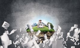Little boy keeping mind conscious. Young little boy keeping eyes closed and looking concentrated while meditating on flying island among flying papers with gray Royalty Free Stock Image