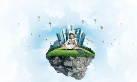 Little boy keeping mind conscious. Young little boy keeping eyes closed and looking concentrated while meditating on flying island in the air with cloudy Royalty Free Stock Images