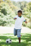 Little boy kicking a football in the park Royalty Free Stock Photography