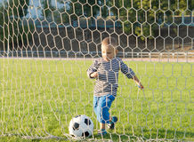 Little boy kicking a goal Royalty Free Stock Photo