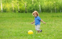 Little boy kicking yellow ball Royalty Free Stock Photo