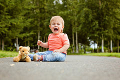 Little boy the kid in blue jeans crying bitterly, sitting on the. Ground next to a soft toy in the summer Royalty Free Stock Photos