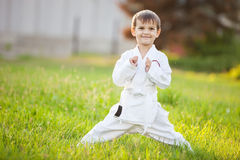 Little boy in kimono standing on grass in park Royalty Free Stock Image