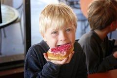 Little Boy-Kind, das Forsted-Donut an der Bäckerei mit seiner Familie isst stockbild