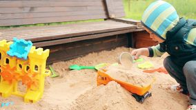 A little boy in kindergarten playing in the sandbox with sand stock footage
