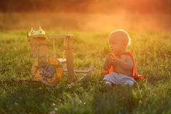Little boy king sits on the grass with the horse toys. The Prince is resting in the open air at sunset with the light beam. royalty free stock photos