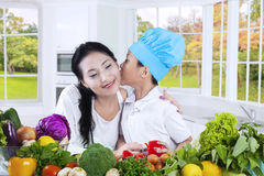 Little boy kiss his mother in the kitchen Royalty Free Stock Photography
