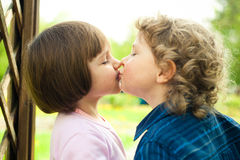 Little boy kisses girl Stock Photos