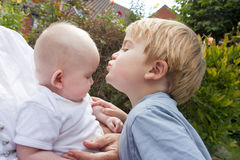Little boy kisses his baby sister Stock Images