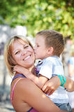 Little boy kisses his happy mother. On the nature Royalty Free Stock Photos