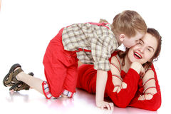 Little boy kisses his young beautiful mother. Mother and son sitting on the floor-Isolated on white background Stock Photos